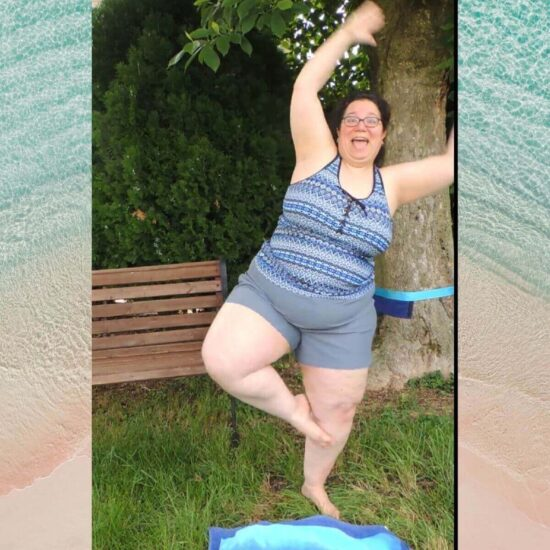 Image of a woman (Jessie) outside in front of a bench and tree, wearing a blue and gray tankini and starting to fall while trying to do the yoga tree pose.