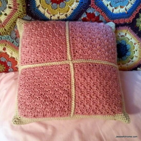 Image of a square pillow with a pink crochet top with gold crochet trim on a pink sheet and multicolored crochet afghan.