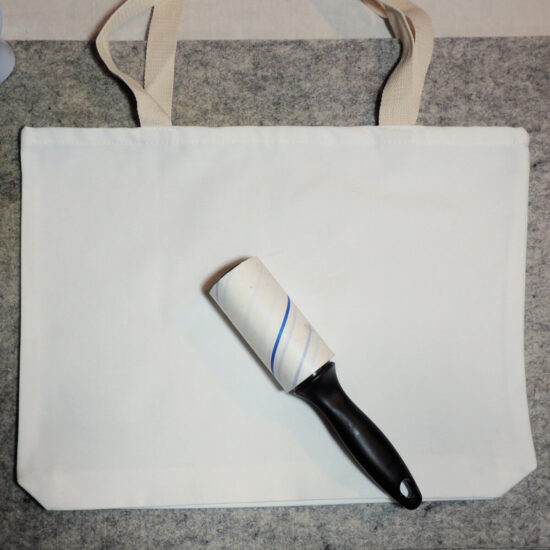A photo of a plain white tote bag laying flat on a gray background, with a link roller on top of it.