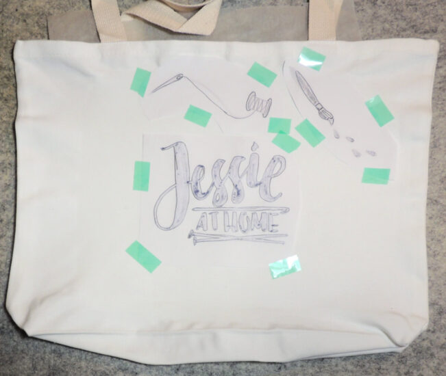 A photo of a plain white tote bag laying flat on a gray background, with various colored art graphics taped face down on it.