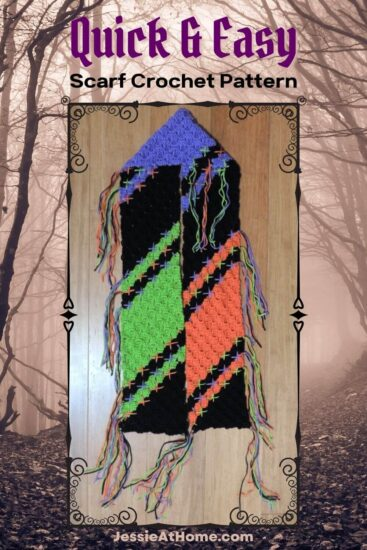 """A vertical rectangular sienna image of a spooky forest. Over most of the image is a black decorative rectangular frame with a image inside of a corner to corner crochet scarf with diagonal lines of black, green, purple, and orange, with stitches at the color changes, laying on a wood floor. Above the frame is text """"Quick & Easy"""" and """"scarf crochet pattern"""". Below the frame is text """"Jessie At Home dot com."""""""